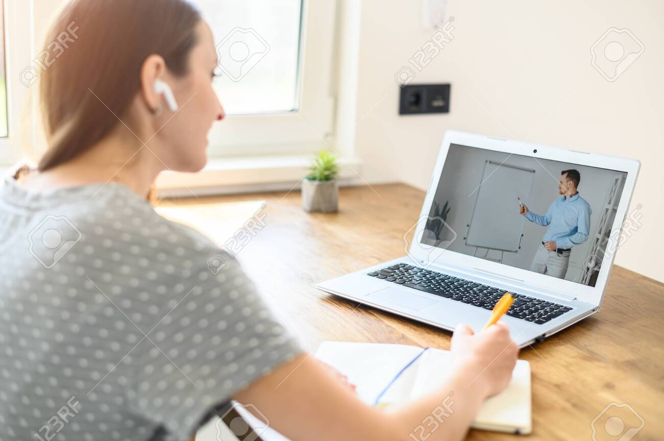 A man is online tutor, teacher with flip chart on the laptop screen, a young woman student is watching and writing. Back view. Online education, online learning - 145528770