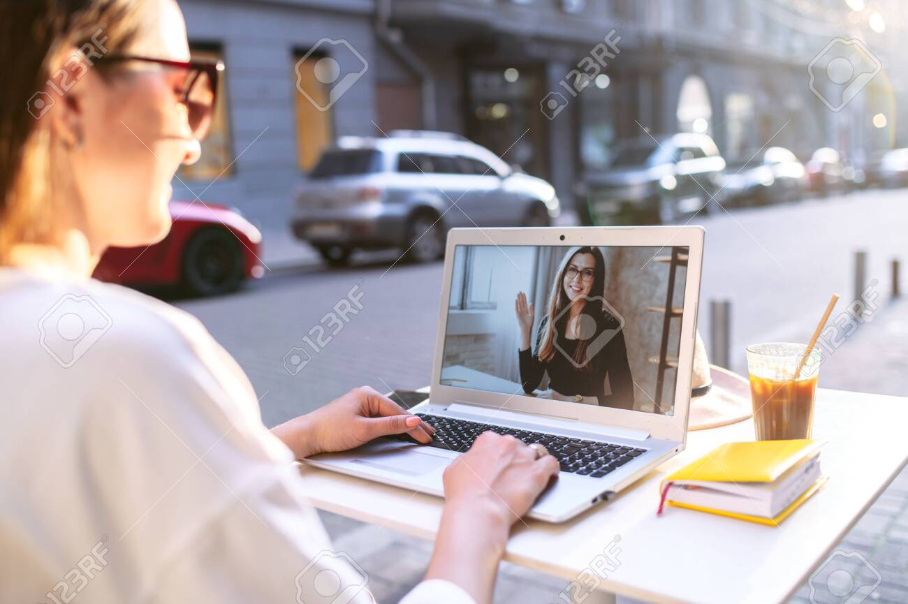 Virtual meeting with a friend. Young woman sits at the table in the street cafe and uses laptop for video call to another woman, two female friends are talking online - 149643513