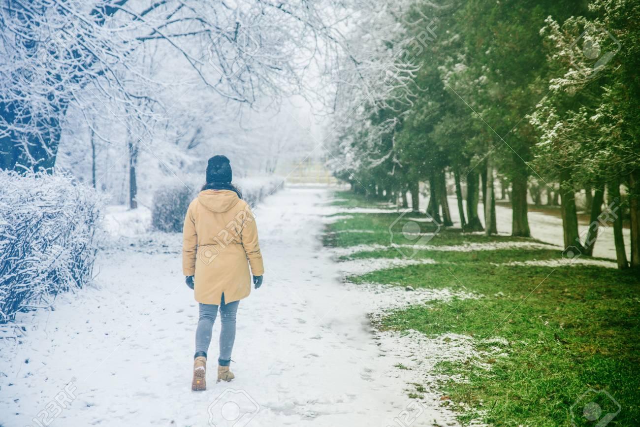 Woman Walk By Park Where Winter Meet Spring Lizenzfreie Fotos