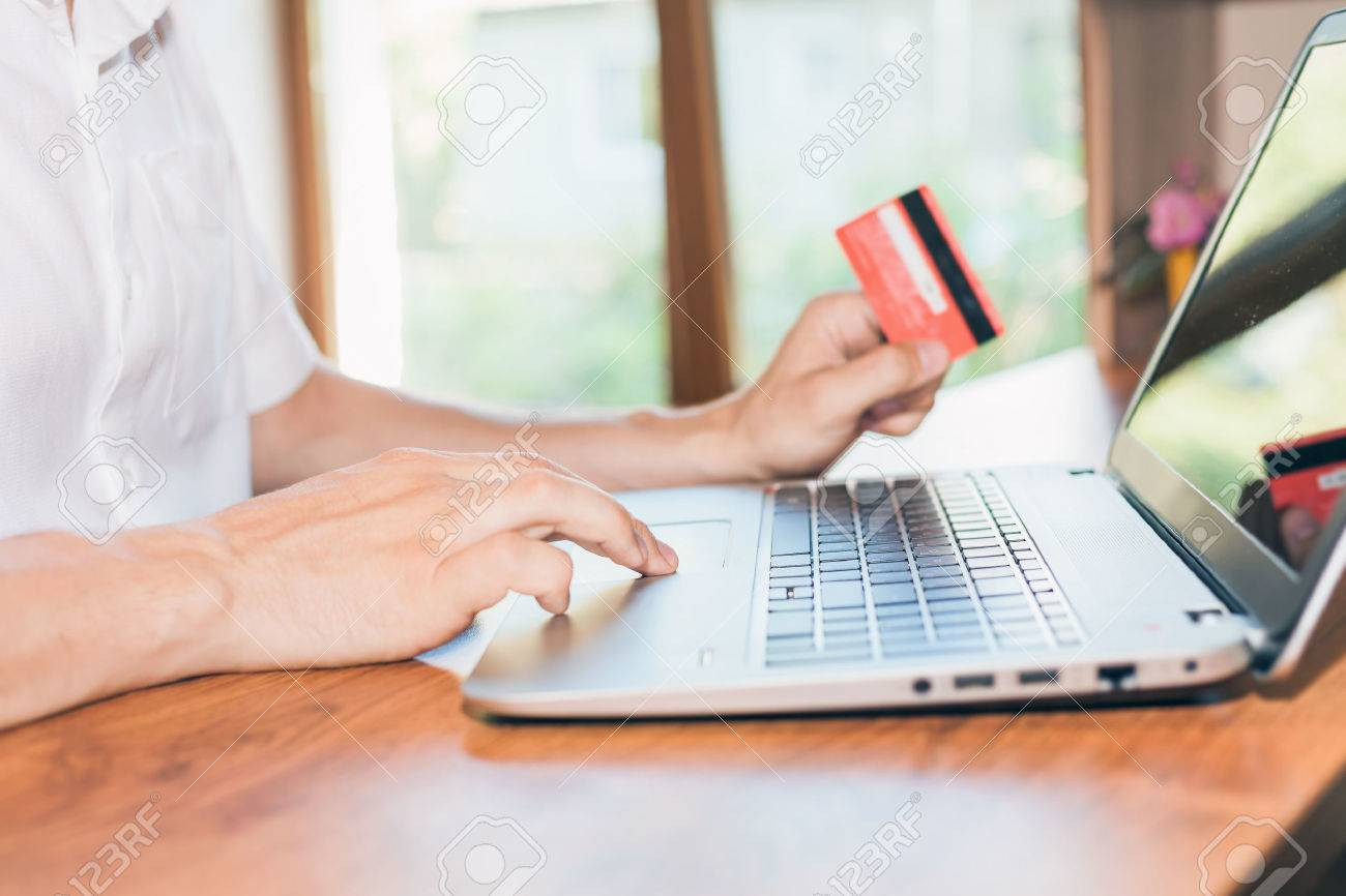 Concept of online payment by plastic card through the Internet Banking. Close-up of human hand for laptop and holding credit card, man is shopping indoor at home - 40708115