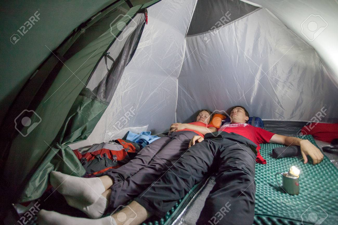 Image Of Sleeping Tourists Inside The Tent Camp On Background Night Lighting Flashlight In