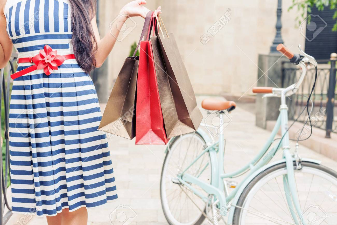 Closeup fashion woman dressed in striped dress with bags and vintage bike has shopping travel to Italy, Milan. She has happy vacation travel to Europe - 43739588