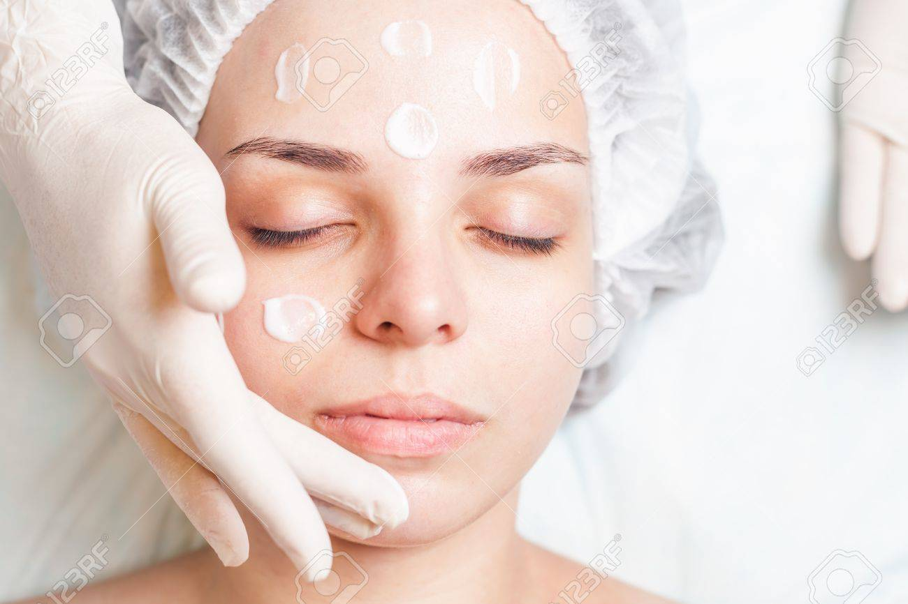 Beautiful young woman in spa salon receiving face treatment with facial cream at white background. Concept of beauty, massage, healthy therapy and relaxing - 43985806