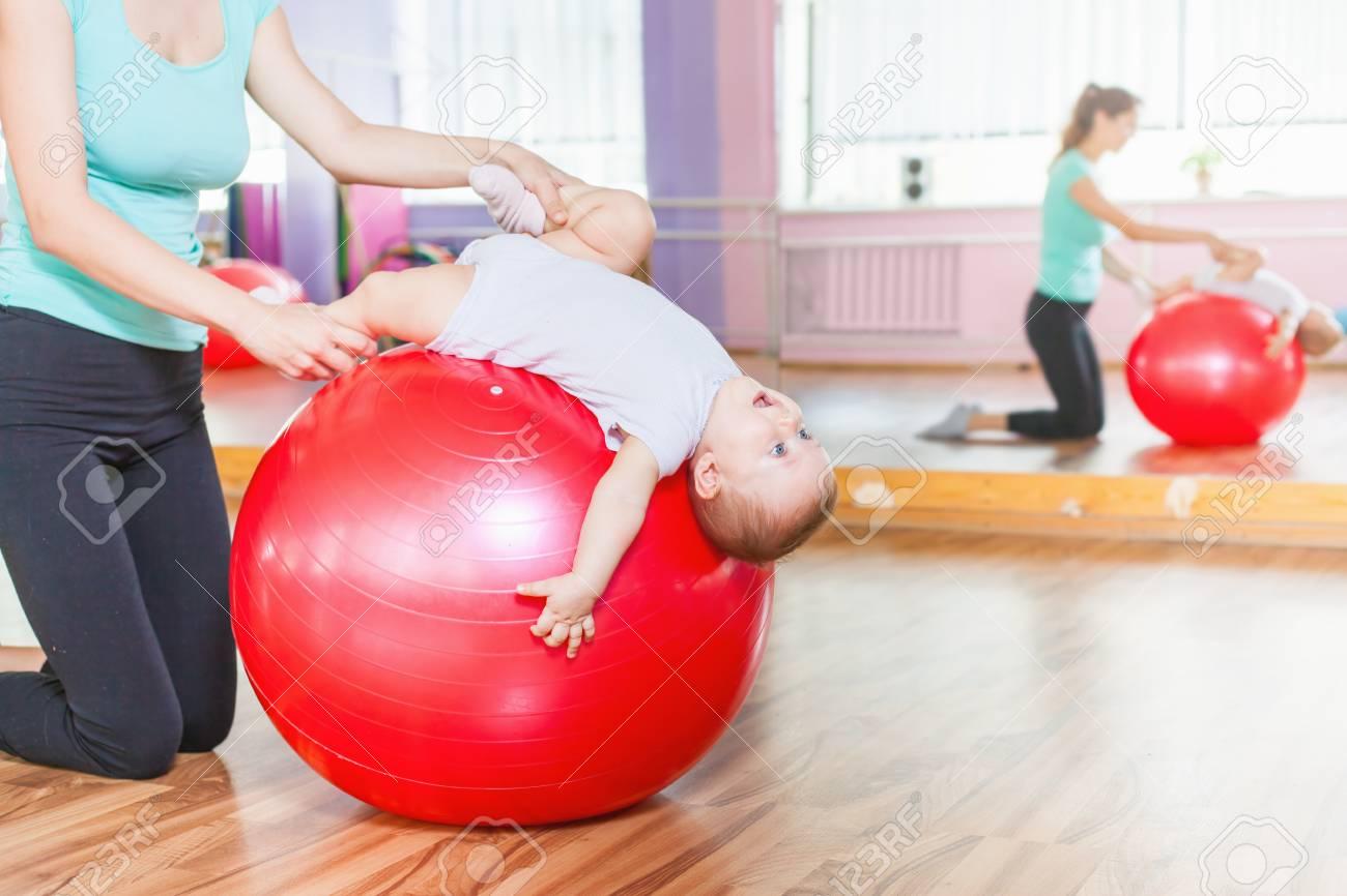 Foto de archivo - Madre con el bebé feliz haciendo ejercicios con pelota de  gimnasia roja en clase de gimnasia. Concepto de cuidado de la salud del  bebé. 24c4f14f3a34