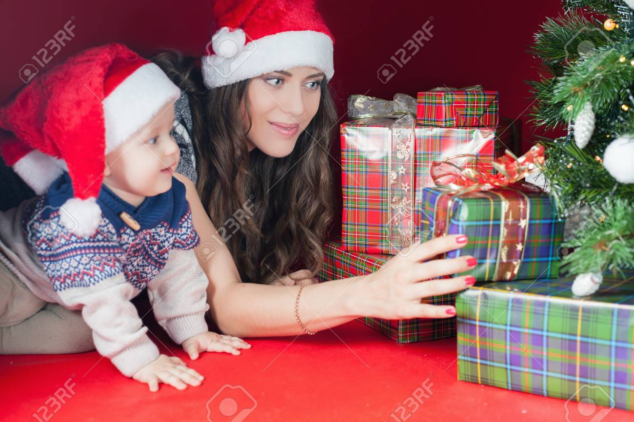 Happy Family Of Baby And Mother Near The Christmas Tree With.. Stock ...