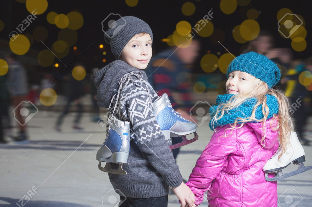 Happy children ice skating at ice rink outdoor, at winter night, sport and healthy lifestyle, ice skating at Holland. Funny kids, boy and girl, sister and brother. Family - 50004474