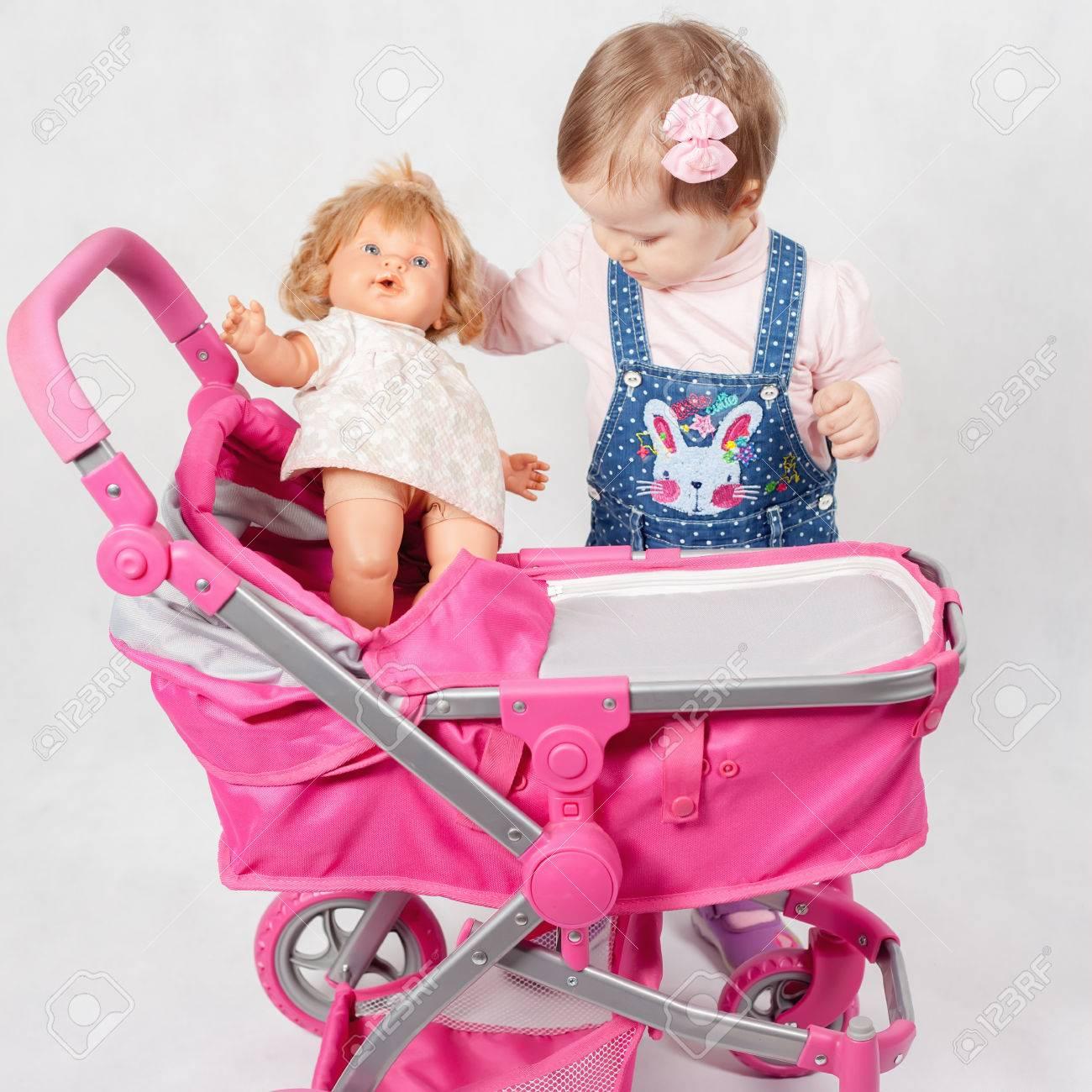 buy popular half price buy good Mignonne petite fille jouant avec la poupée et la poussette de bébé.  Landau. Magasin du monde des enfants. Vêtements pour enfants
