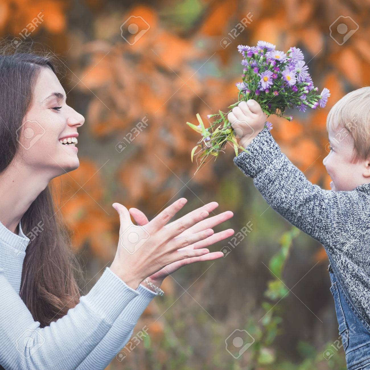 Child gives to happy mother flowers fall colors background happy family values baby