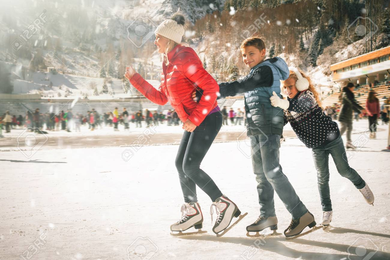 family outdoor activities. Happy Family Outdoor Ice Skating At Rink. Winter Activities Stock Photo - 88492049
