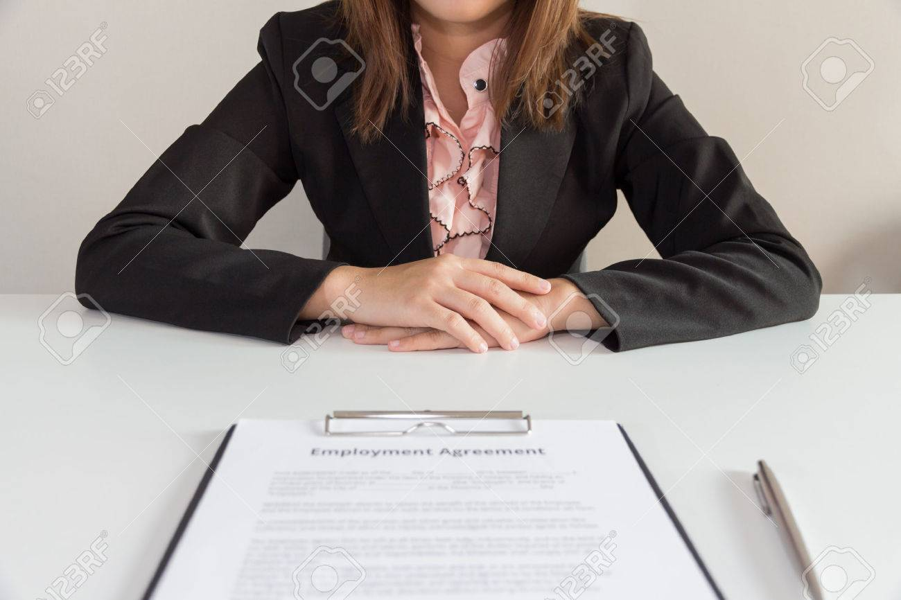 Businesswoman sitting with employment agreement in front of her. - 55276389