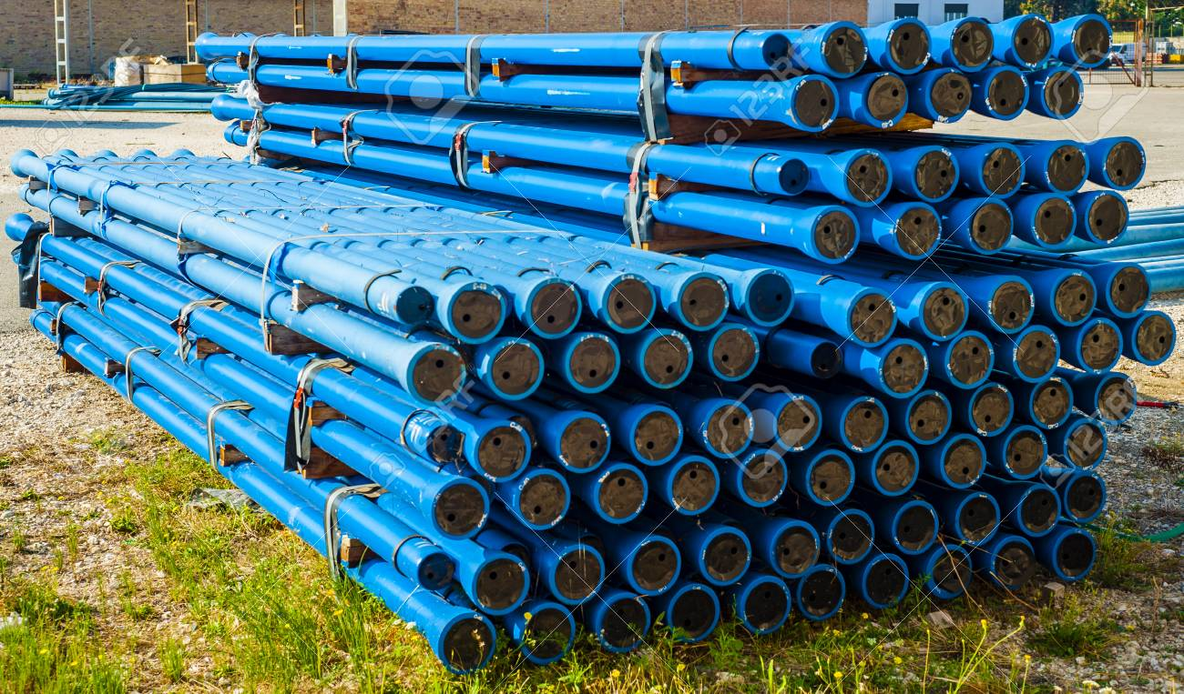 Stacks of blue PVC water pipes in stack on open storage at an