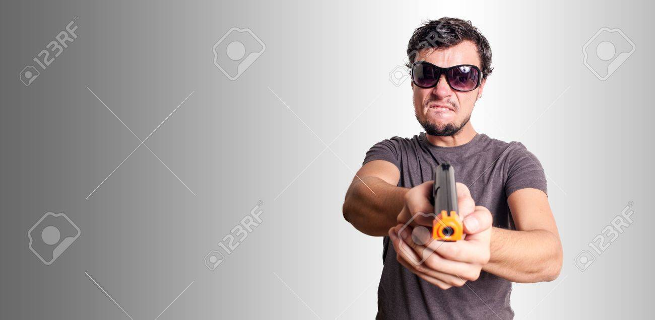 bad guy with gun on grey background Stock Photo - 16549644