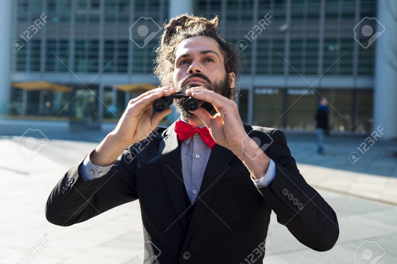 Stylish elegant dreadlocks businessman binoculars in business landscape Stock Photo - 24333153