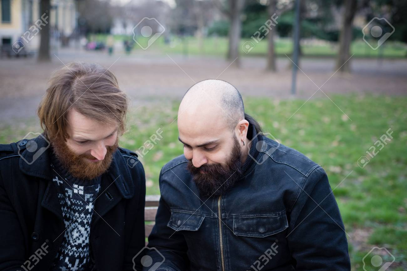 two bearded modern man working on tablet at the park Stock Photo - 26304172