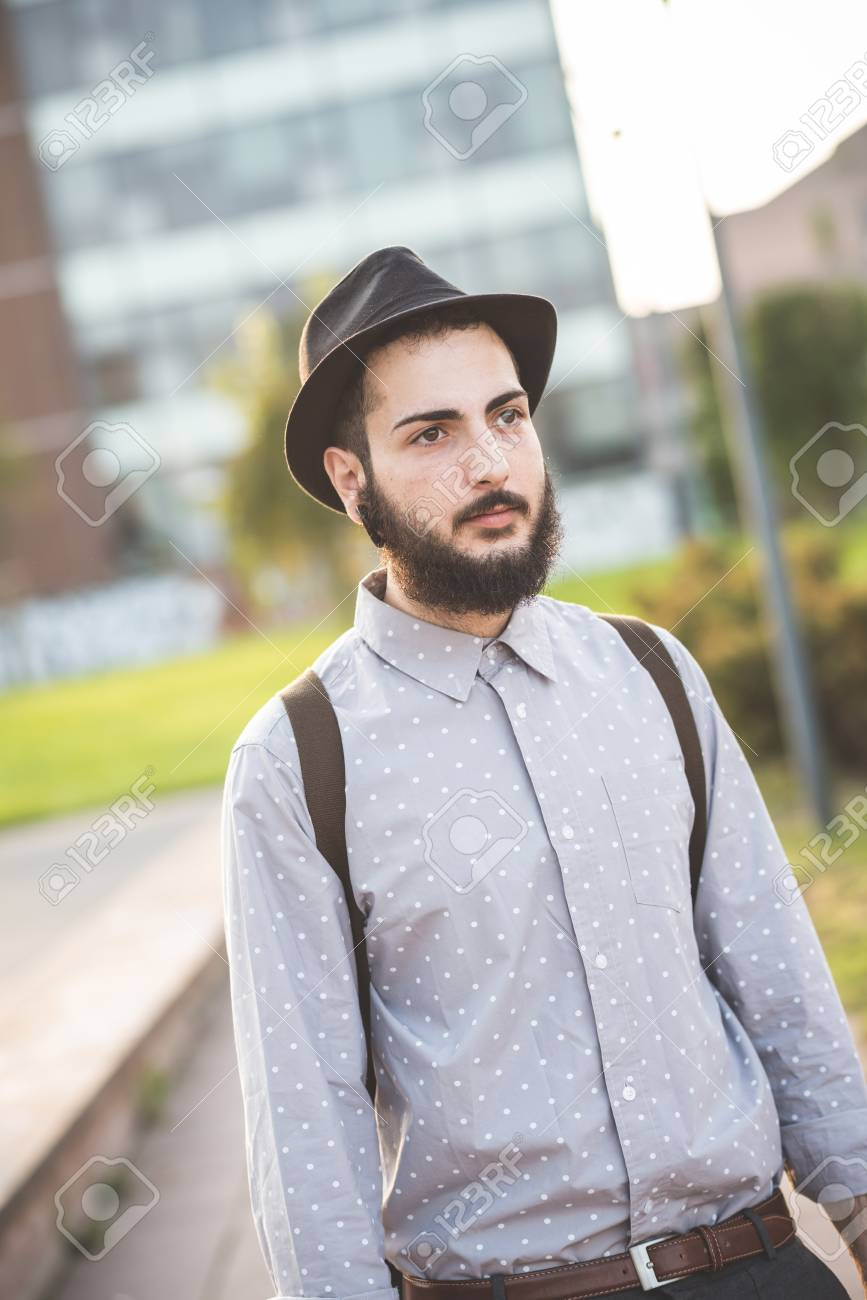 Stock Photo - young handsome hipster gay modern man in town