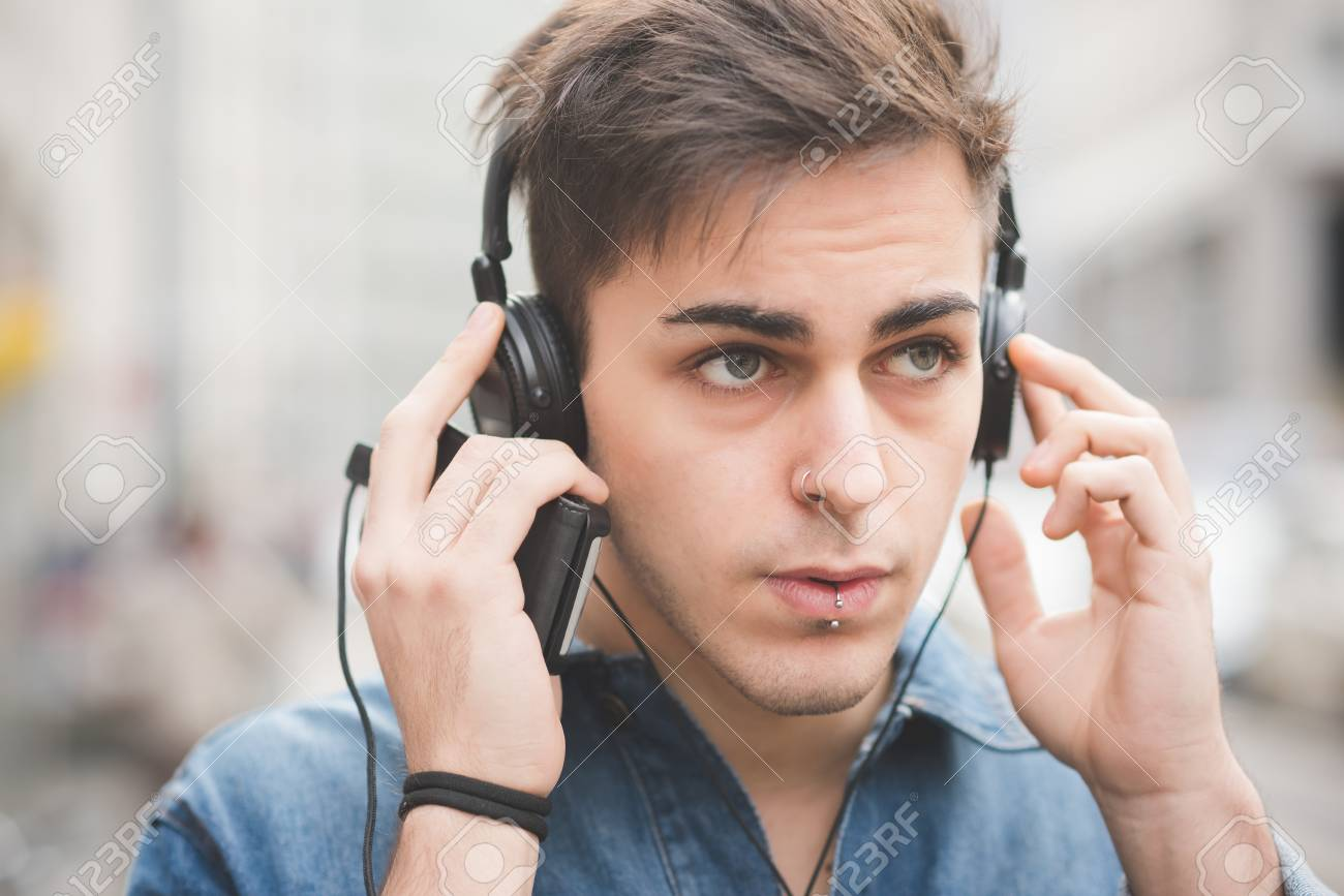 Portrait of young handsome alternative dark model man listening