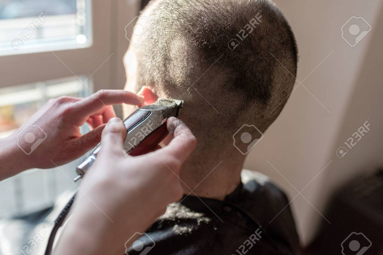 Close Up On Woman Barber Hand Cutting Hair Using Razor Stock Photo