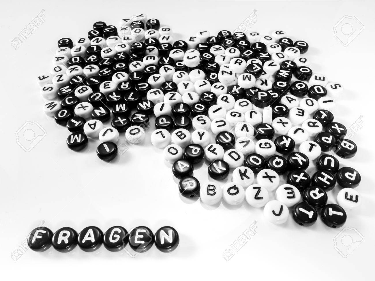 heap of round letters black and white and quotes word written in question written by side; fragen - 55371369