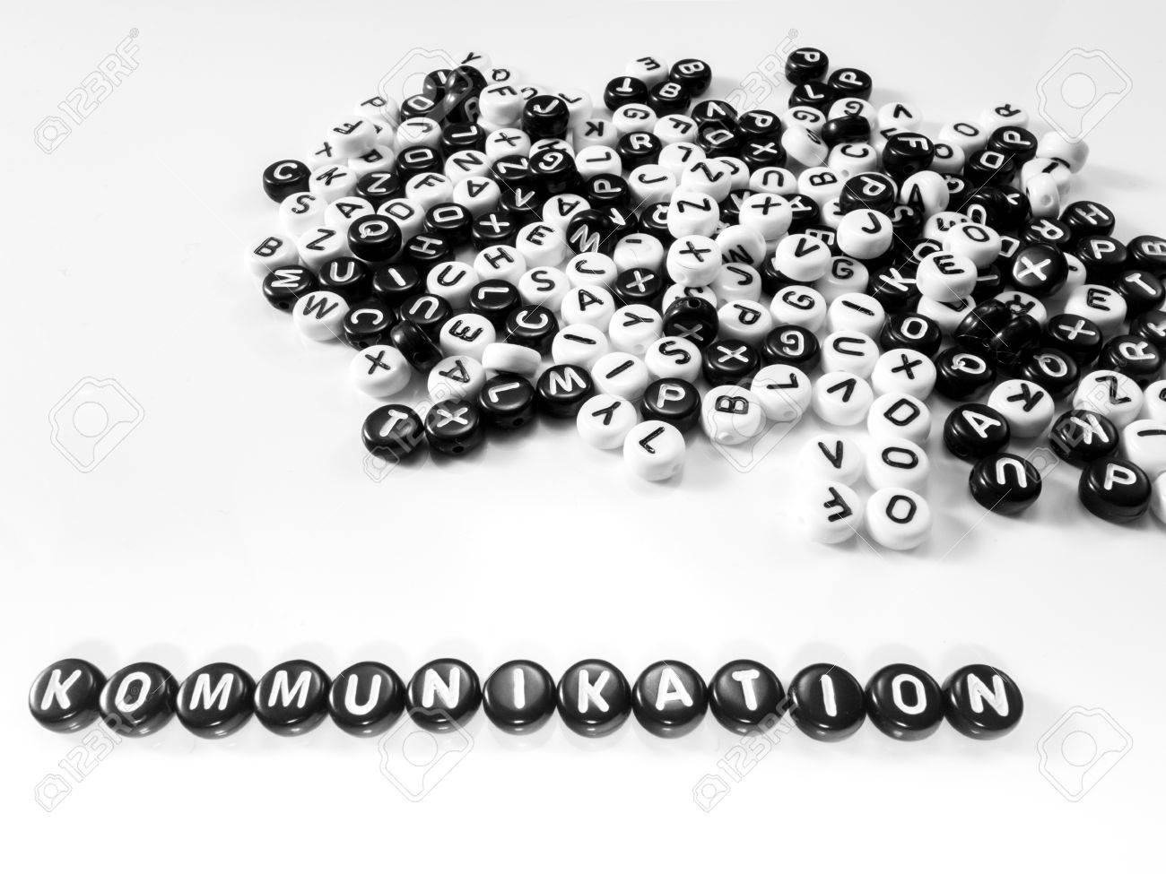 heap of round letters black and white and communication word written in german written by side; kommunikation - 55371378