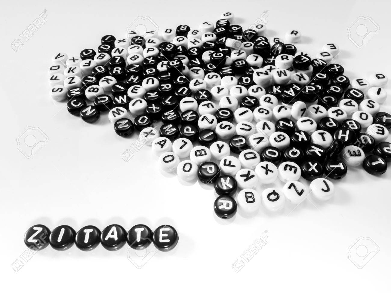 heap of round letters black and white and quotes word written in german; zitate - 55371413