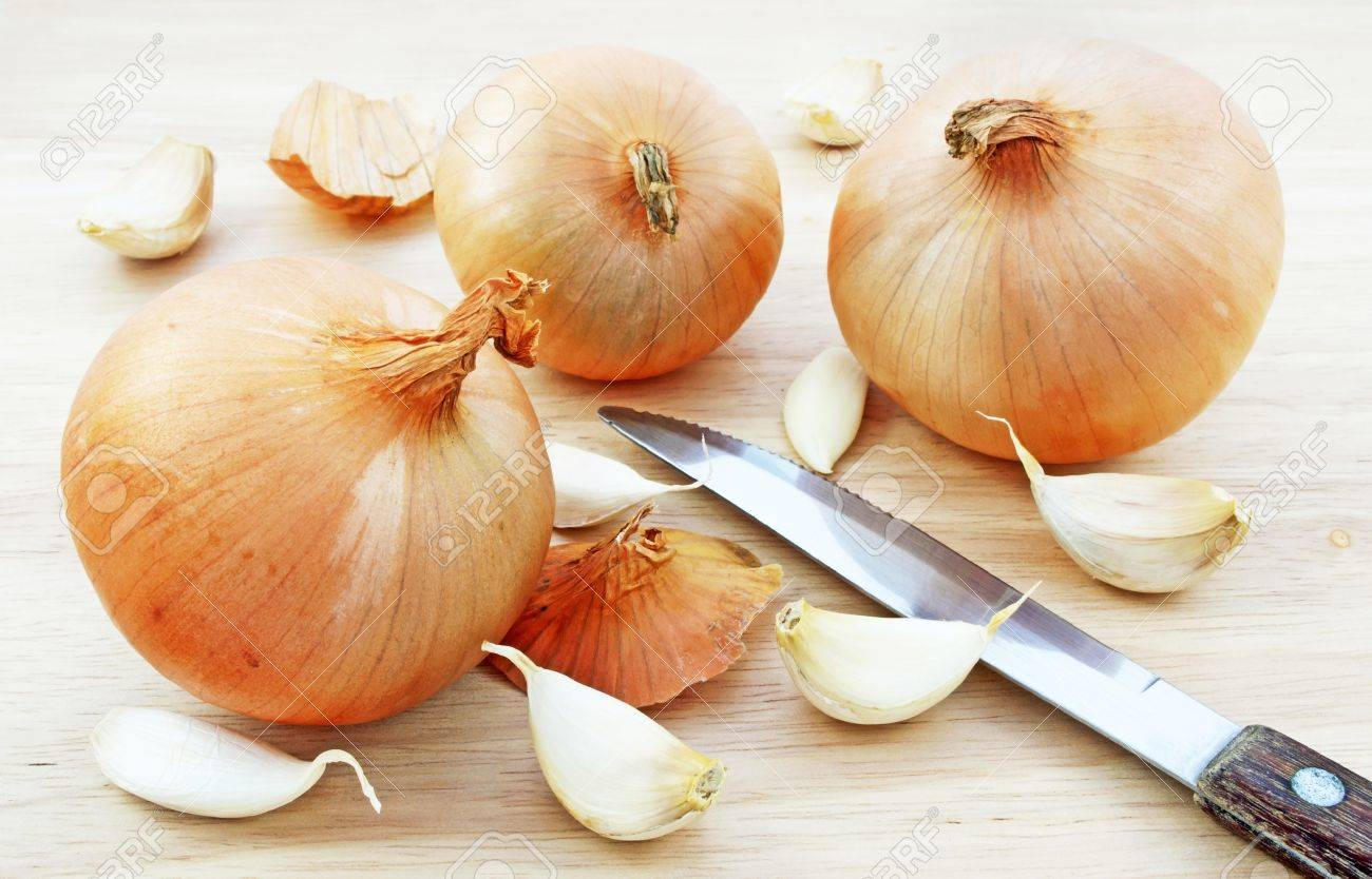 Onion and garlic on chopping board - 12025123