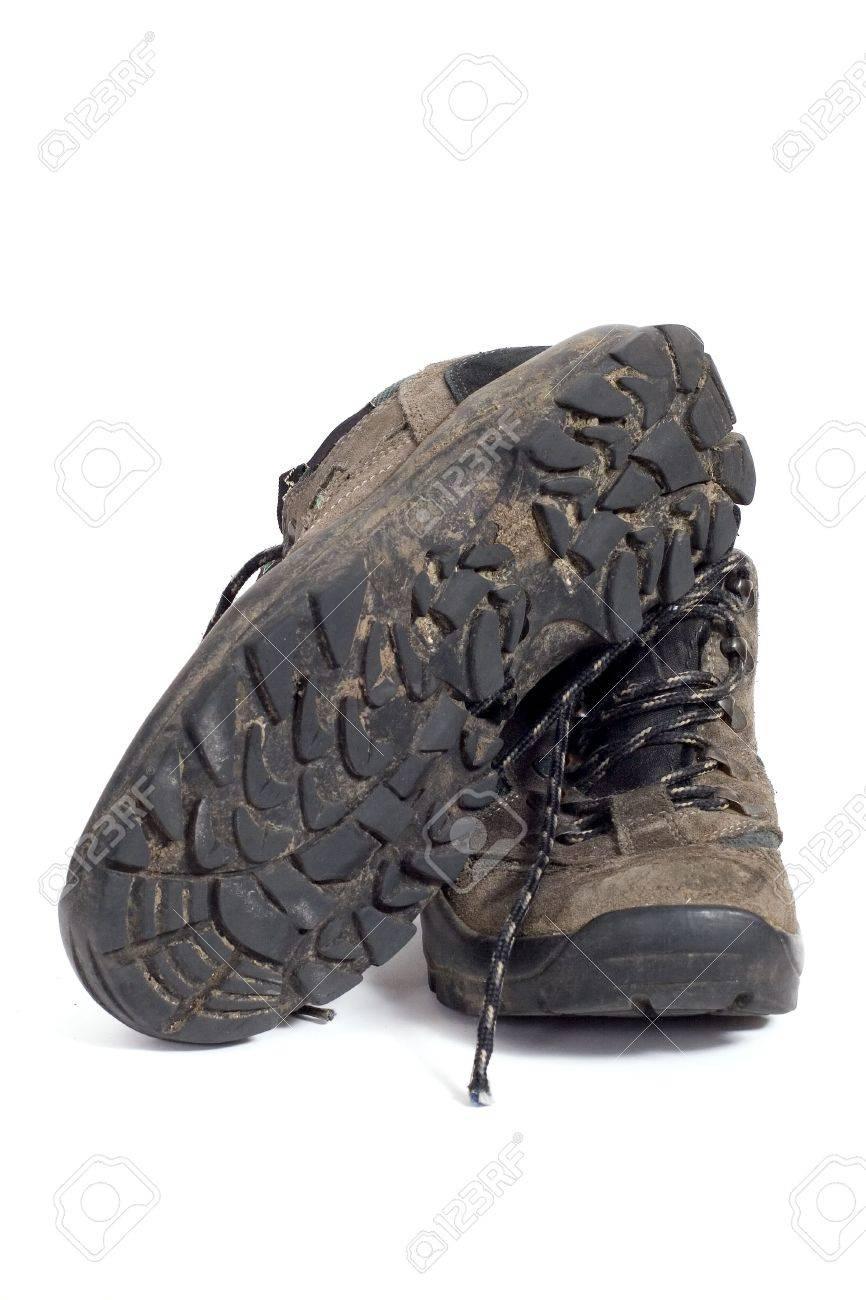 Une paire de chaussures de randonnée sale sur un fond blanc