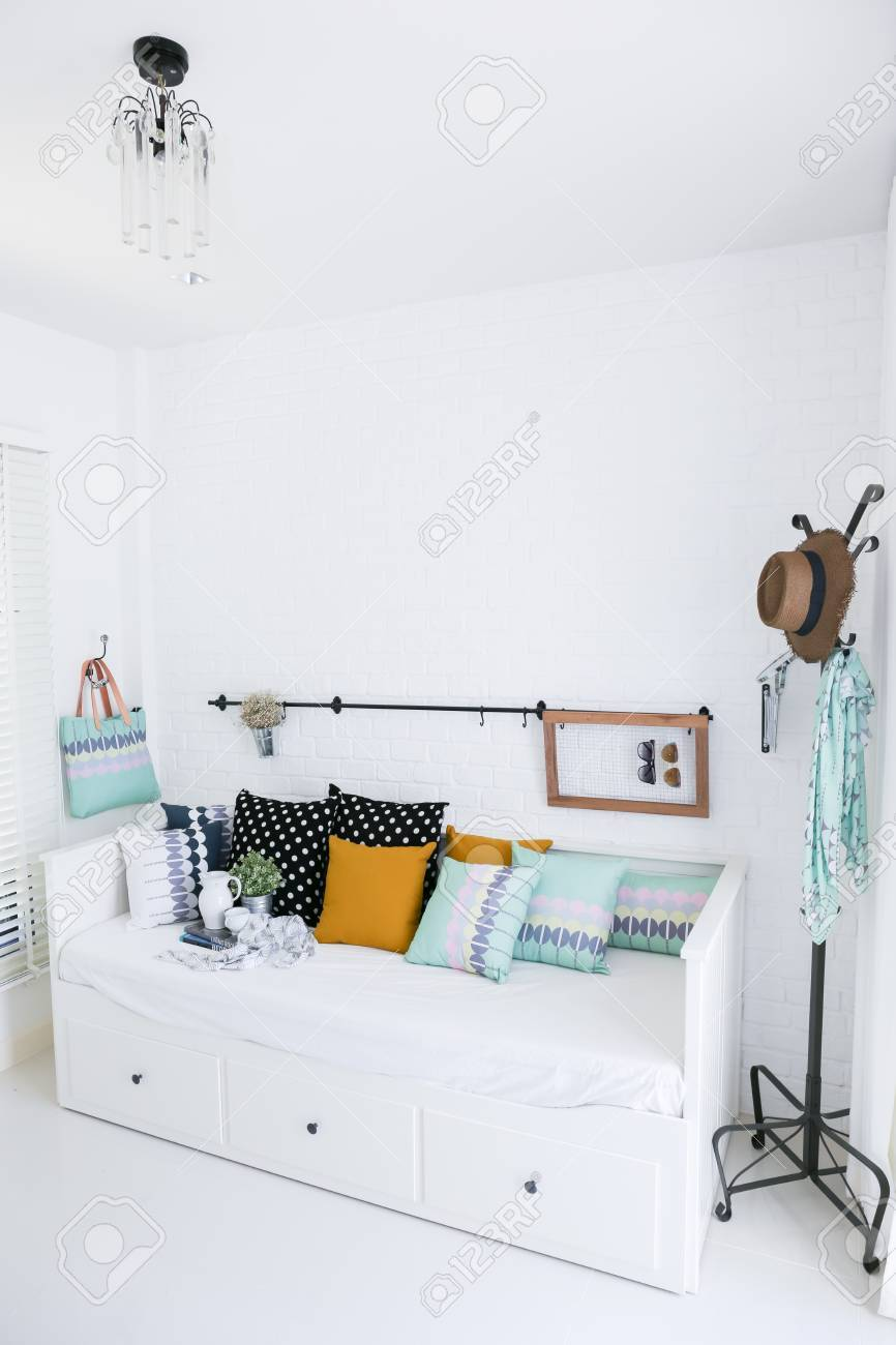 Colorful pillows on a sofa with white brick wall in background Stock Photo - 19459223