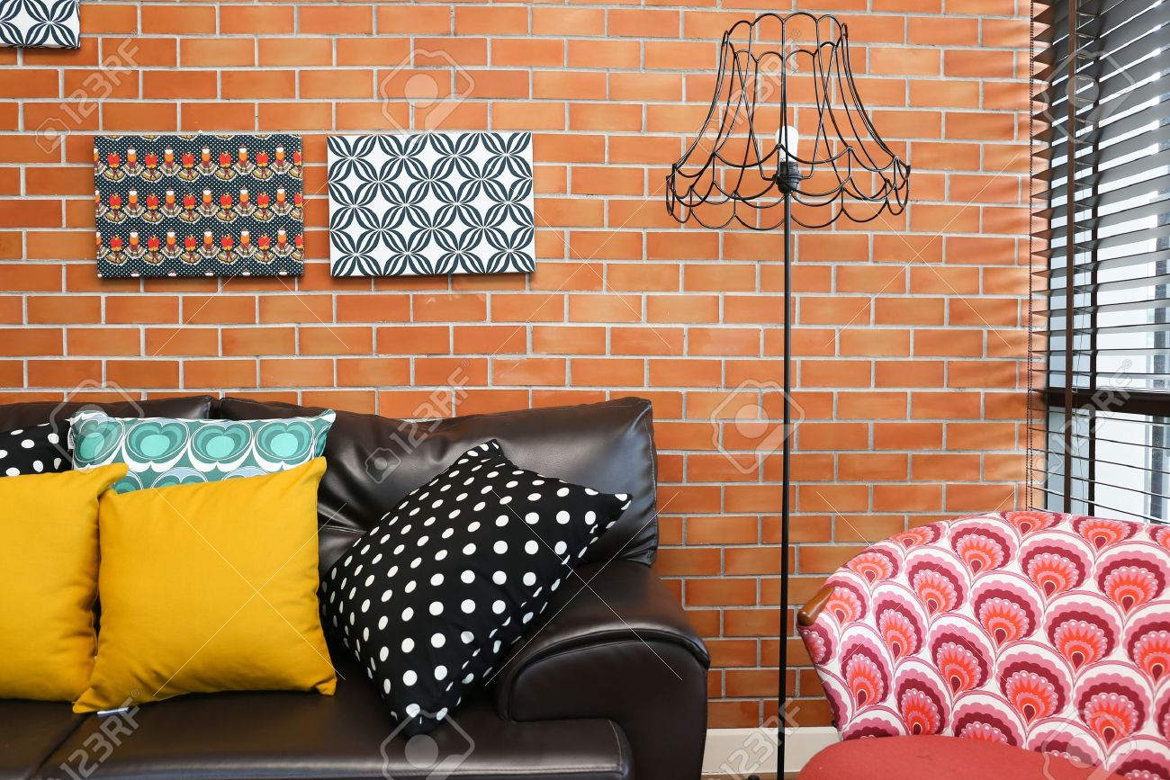 Colorful pillows on a sofa with brick wall in background Stock Photo - 19533282