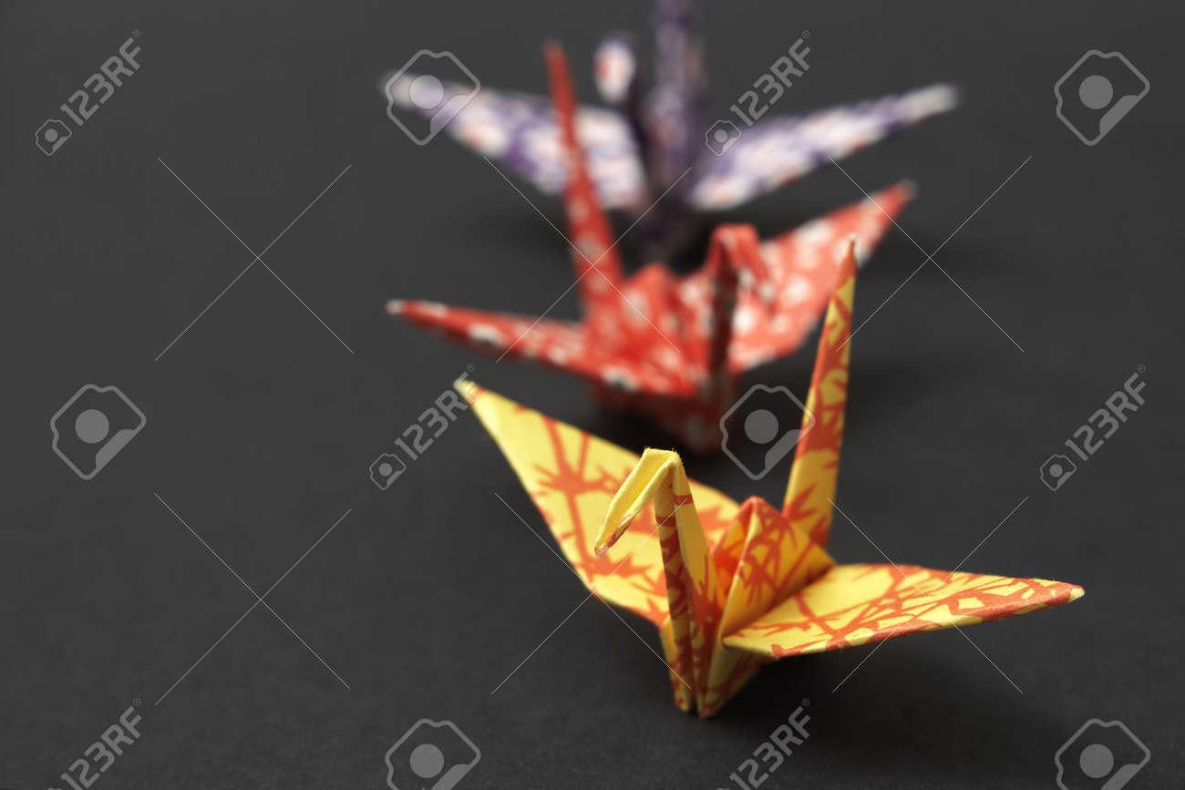 Three origami cranes on a black ground Stock Photo - 3610424