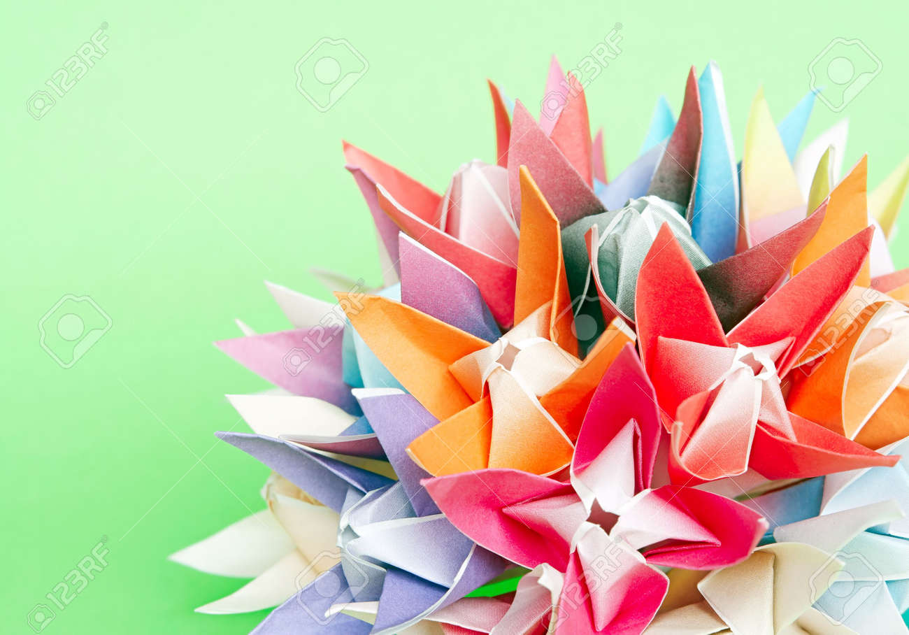 A Colourful Origami Flower Ball On A Green Background Stock Photo