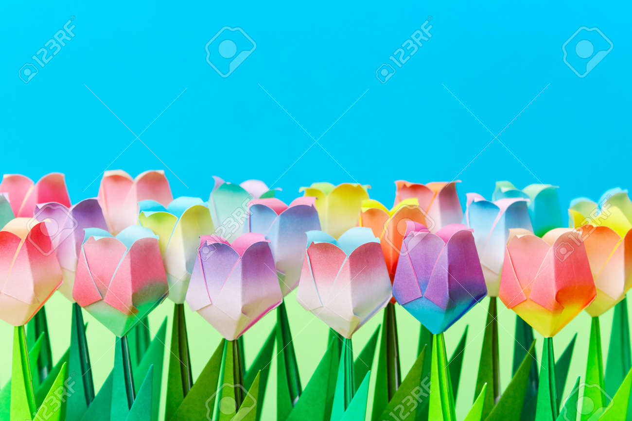 Paper tulips field with a blue background. Shallow depth of field. Focus on the front row. Stock Photo - 6821522