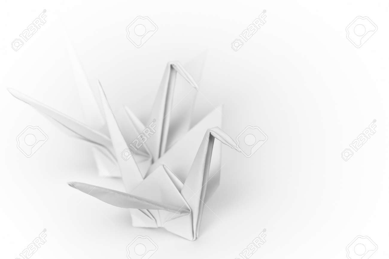 Two white paper birds next to each other on a white background. Shallow depth of field. Stock Photo - 9211475