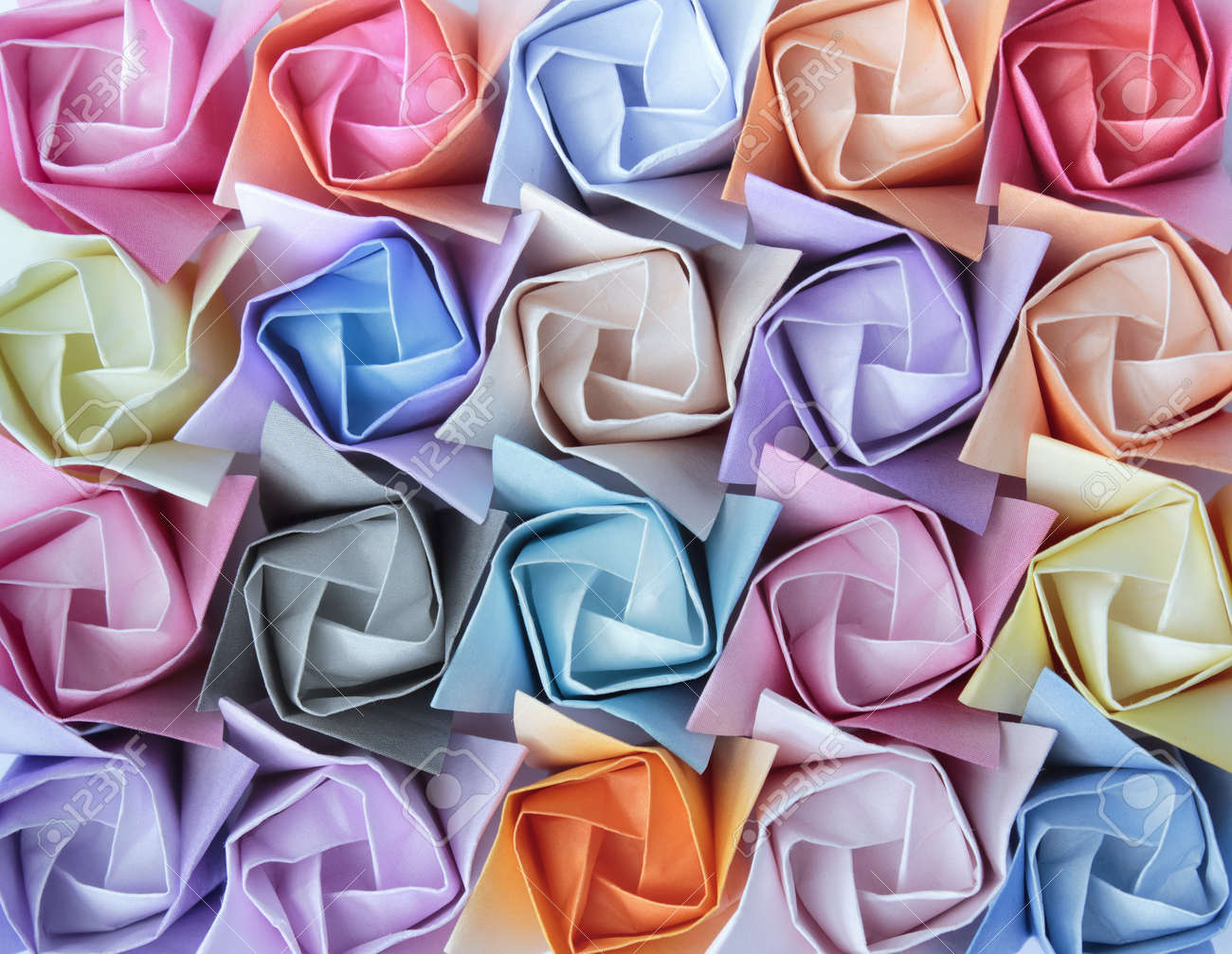 Top view of twenty colourful paper roses arranged as a decorative background Stock Photo - 9240633