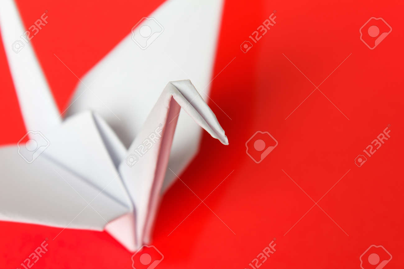 A white paper bird on a red background, shallow depth of field Stock Photo - 9420770