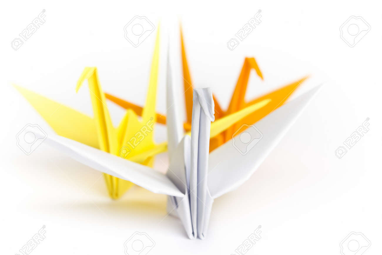 Three paper birds facing different directions on a white background, shallow depth of field Stock Photo - 9442037