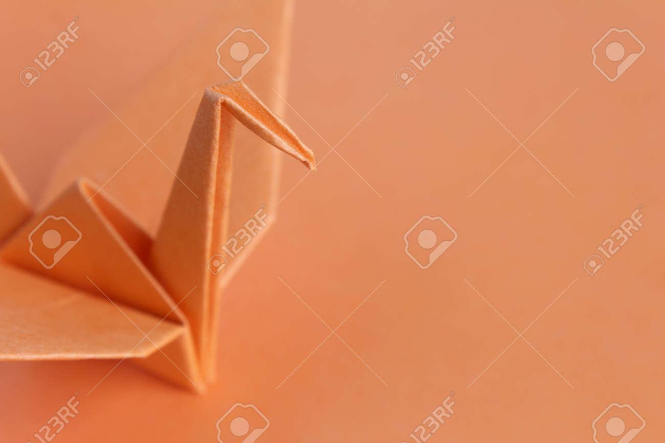 An orange paper bird on an orange background, shallow depth of field Stock Photo - 9526180