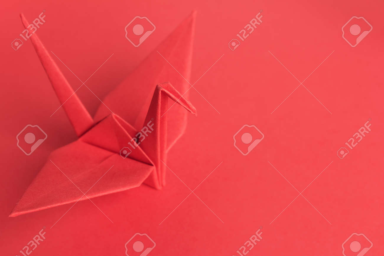 A red paper bird on a red background. Shallow depth of field Stock Photo - 13566018