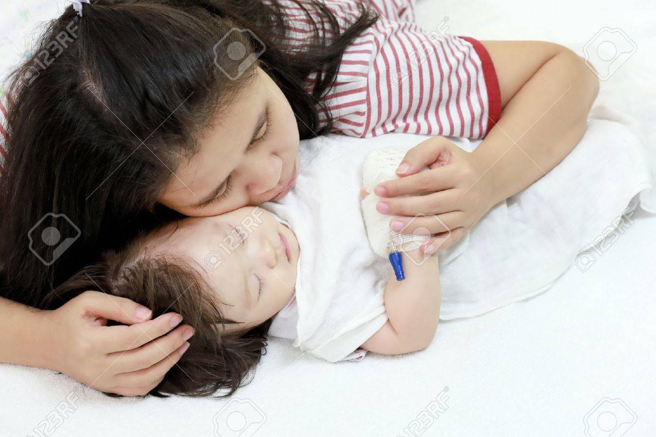 Sick child in her mother's arms. - 19908029
