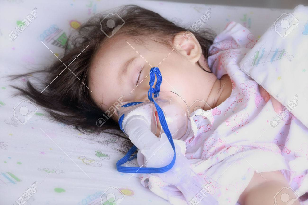 baby girl with a mask for inhaler in hospital. - 24039462