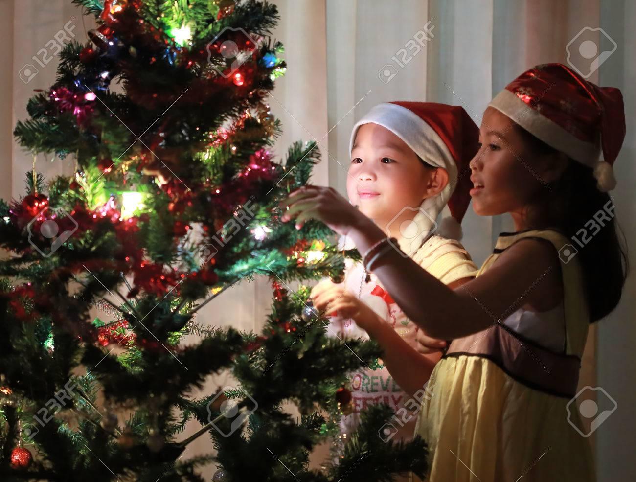 Portrait of happy girl decorating Christmas tree - 24327844