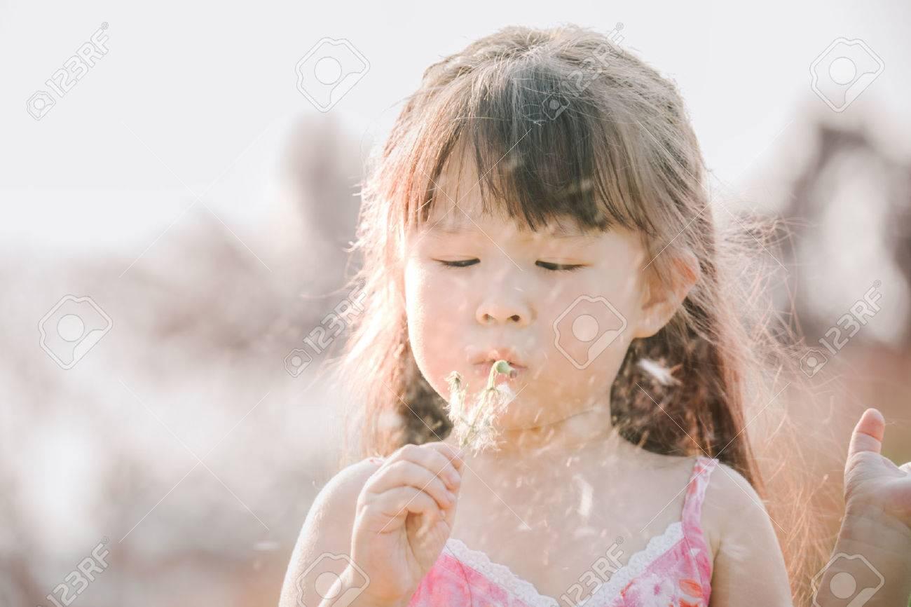 Little asian girl blowing away dandelion flower - 52475691