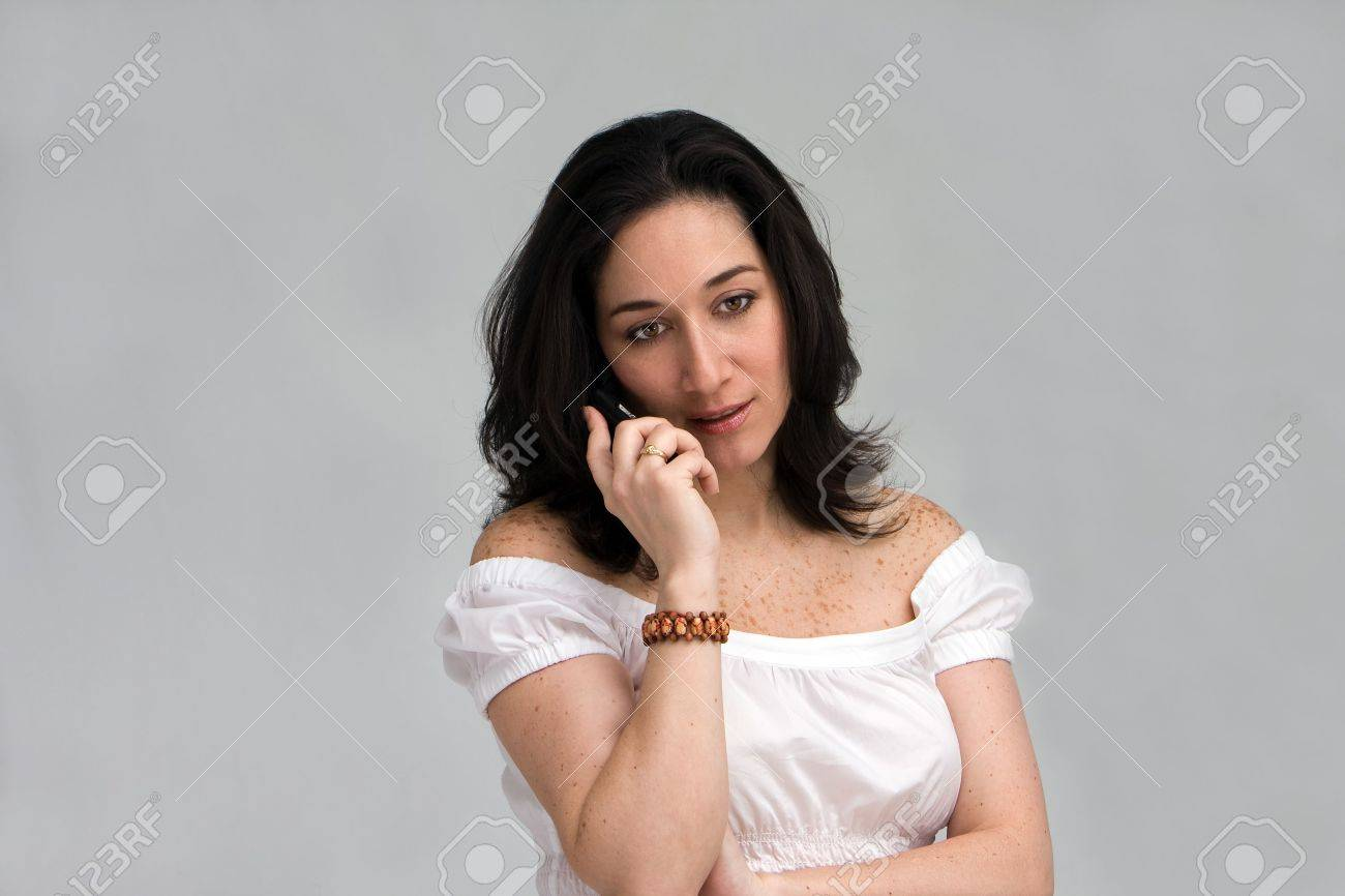 A beautiful latina lady listening/paying attention on a cell phone, isolated on white Stock Photo - 3129632