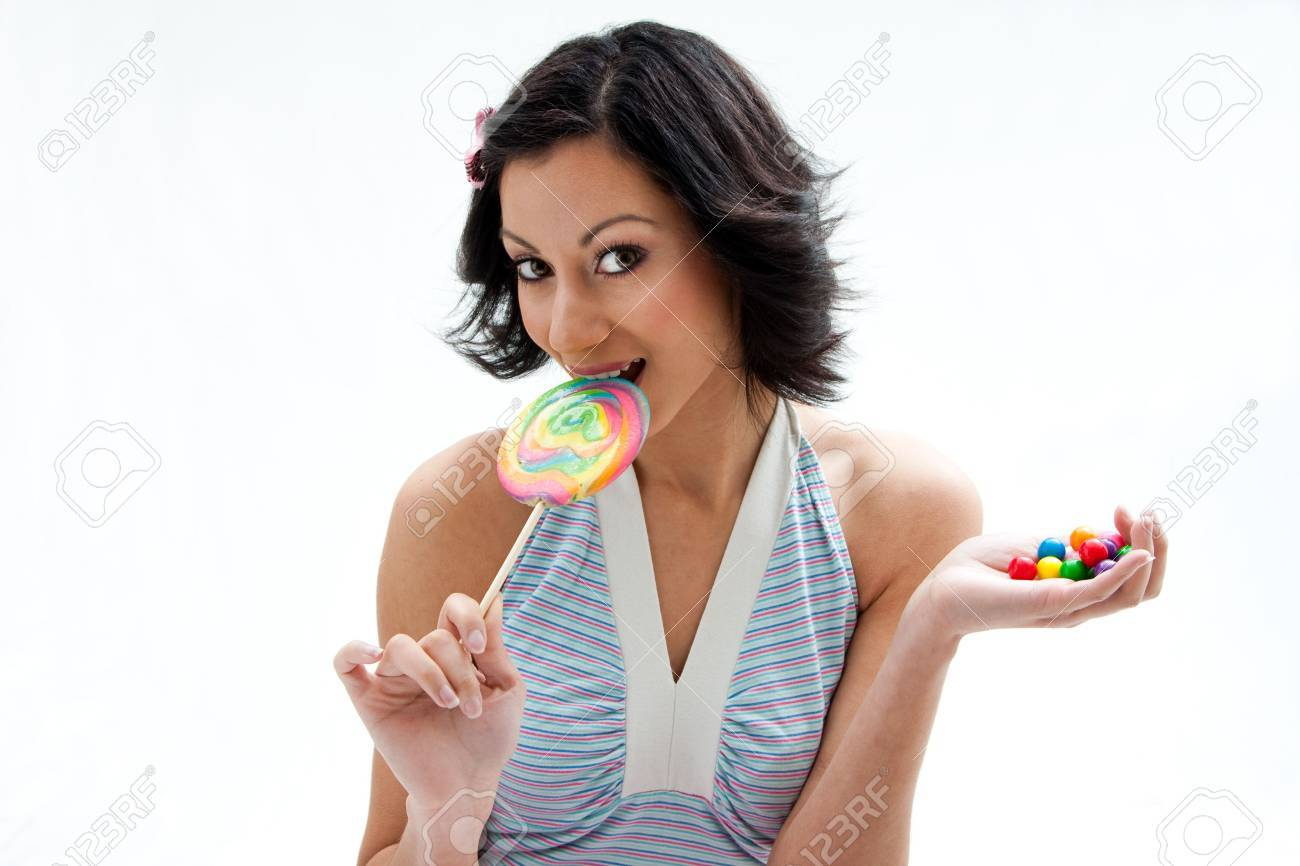Happy beautiful candy girl with a hand full of colorful bubblegum candy balls licking a lollipop, isolated Stock Photo - 4193252