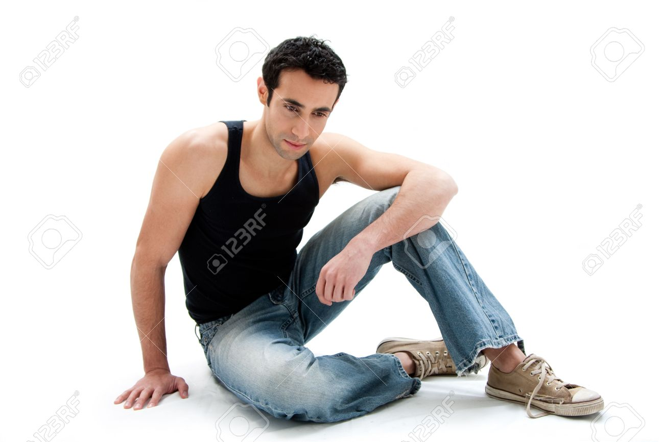 Handsome Caucasian guy wearing black tank top and jeans sitting on floor looking down, isolated - 4278039