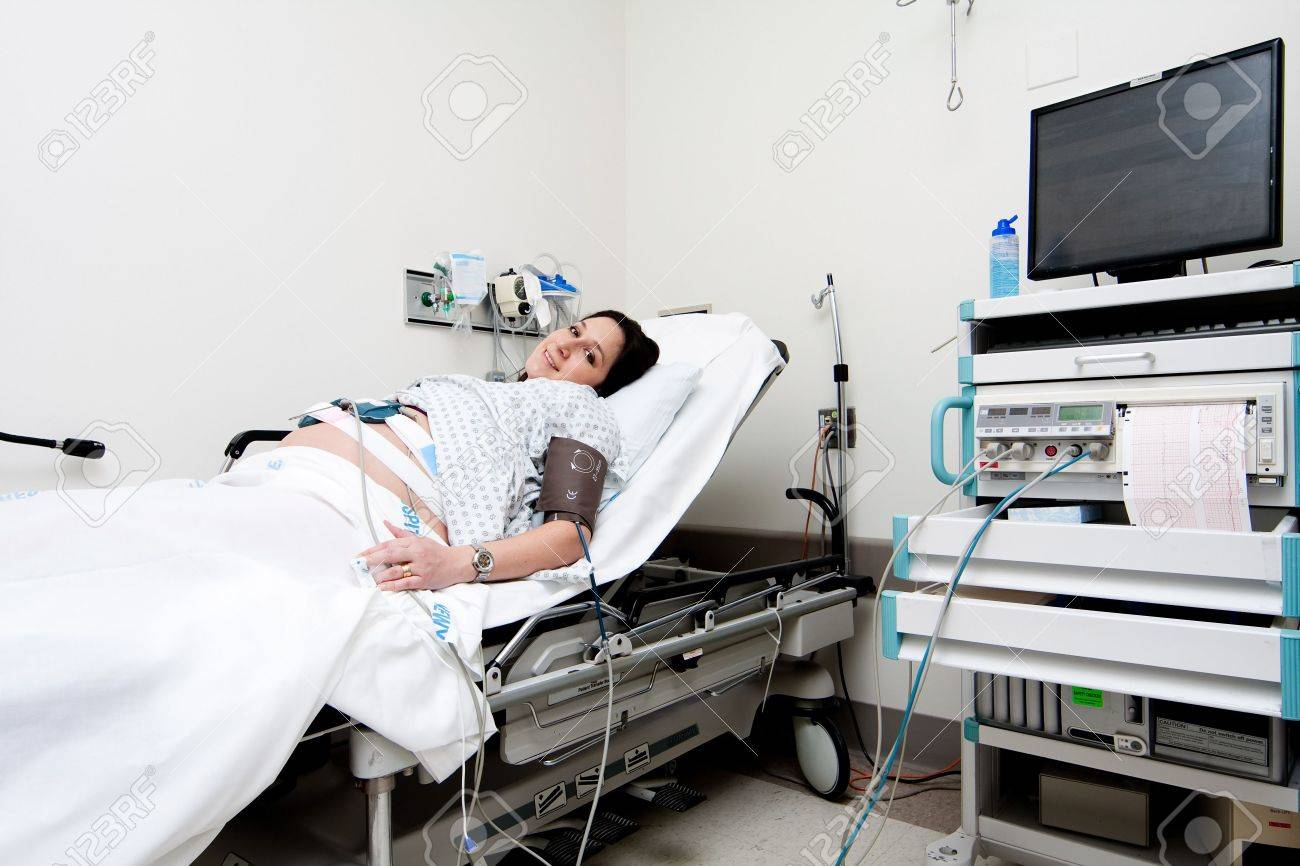 Pregnant Caucasian Hispanic Latina woman laying in a hospital gurney bed in the triage unit doing a medical non stress test (NST) while being hooked up to a computer for monitoring. Stock Photo - 5993571