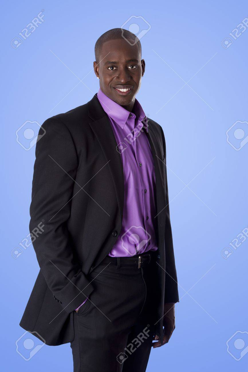 Handsome happy African American corporate business executive man smiling, wearing black suit with purple shirt, standing with authority with hand in pocket,  isolated. Stock Photo - 7098646