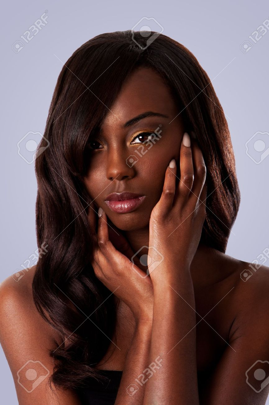 Beautiful face of an attractive African black woman with almond shaped eyes and long wavy hair and hands in her face, isolated. Stock Photo - 8736182