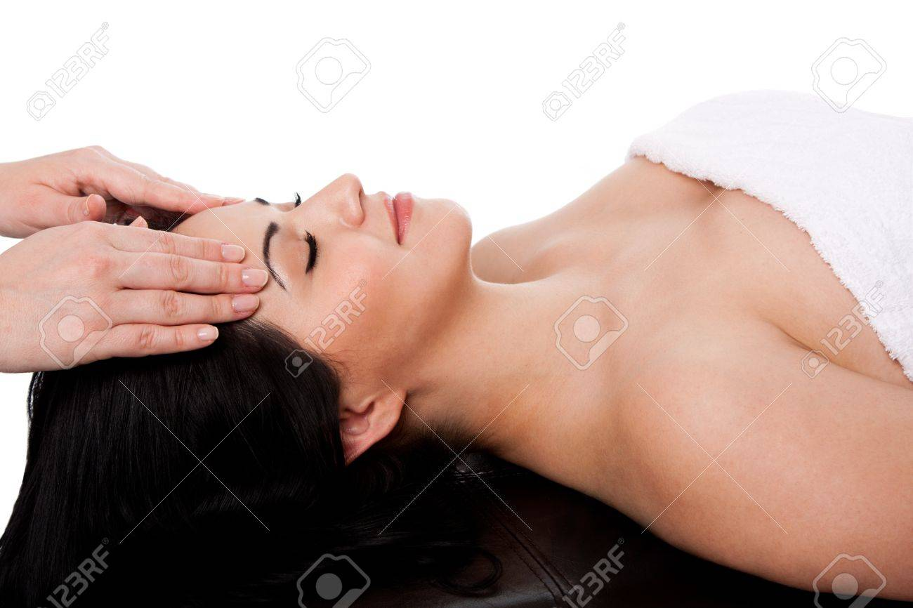 Beautiful happy young woman at day spa getting facial massage beauty treatment laying in white towel, isolated. Stock Photo - 12611566