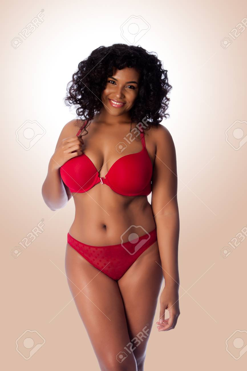 e63f594438 Beautiful happy plus size sexy woman with curly hair in red lingerie bra  and thong underwear