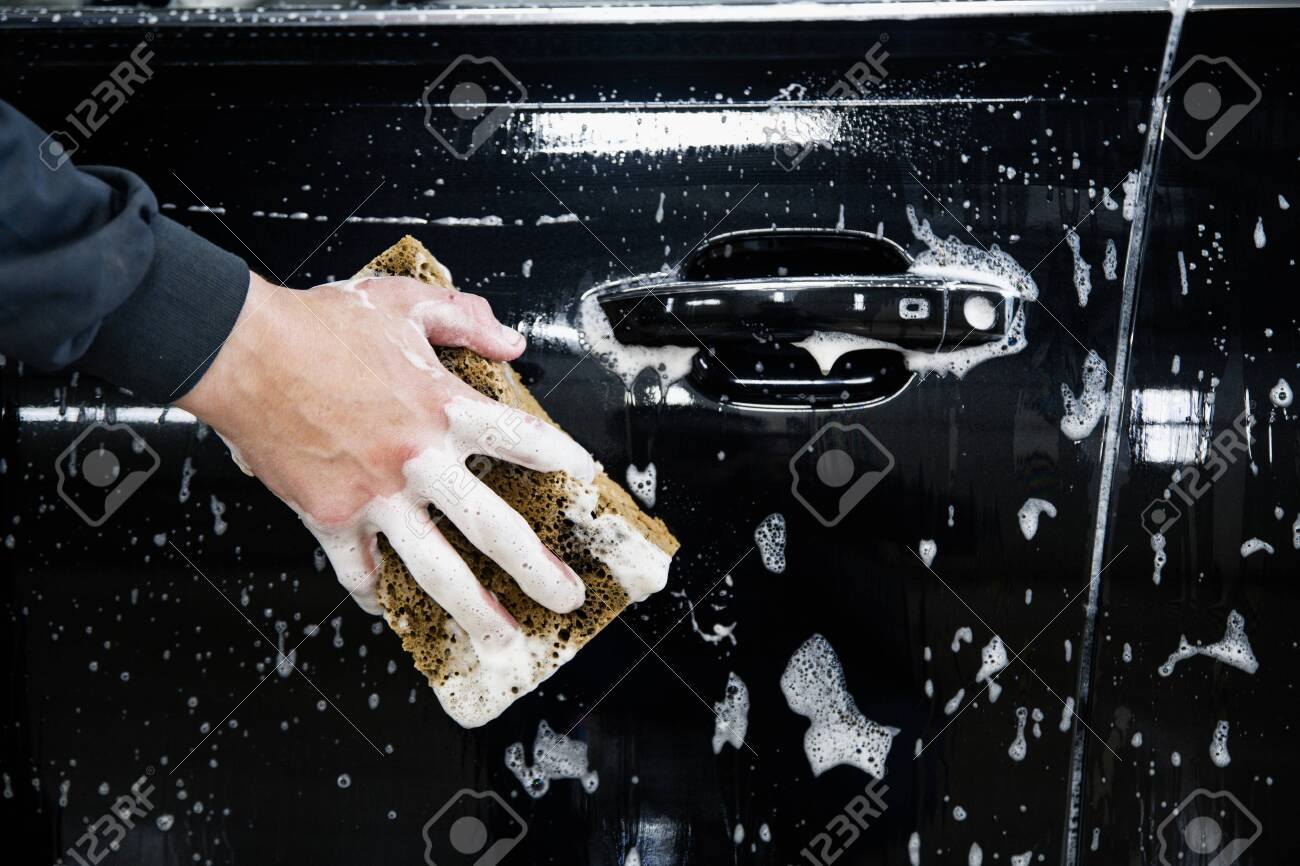 car door with foam and a hand with a foam sponge - 131914373